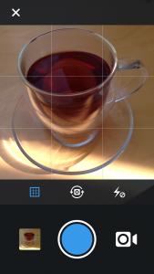 Nach dem Öffnen der App, wählt man das kleine Kamera-Symbol. Nun erscheint folgender Bildschirm. Der blaue Punkt ist der Auslöser. Mit der kleinen Kamera kann man in den Video-Modus wechseln. Darüber kann man das Raster ein-/ausschalten, die Kamera umschalten oder den Blitz ein-/ausschalten.